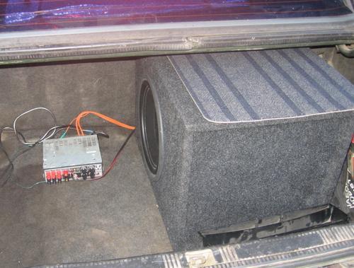 Сабвуфер и усилитель установлены в багажнике автомобиля.
